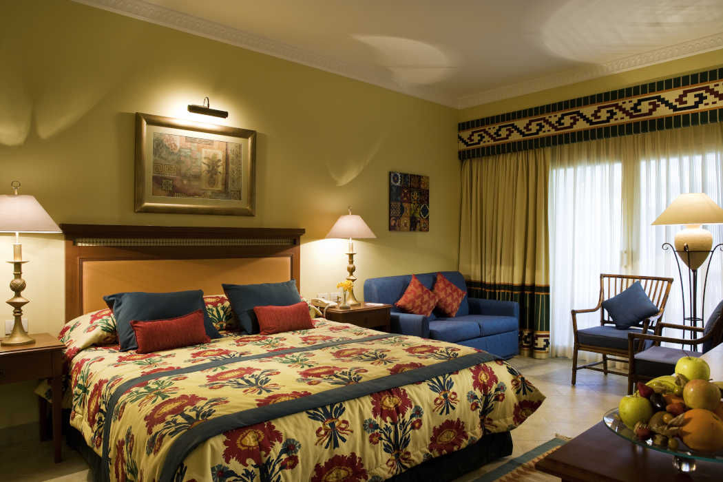 The luxury king bed in blue and beige decoration and a touch of red in pillows at Mosaique Beach Resort in Taba Egypt