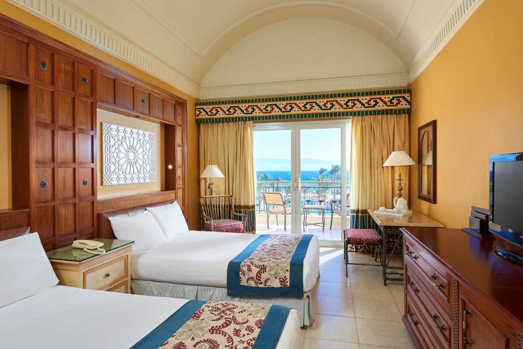 The overview of the twin bedding room at Mosaique Beach Resort and a balcony with Red Sea view