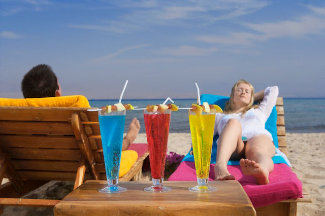 A couple relaxes by the beach of Sinai Bay with served refreshing drinks at Taba Heights