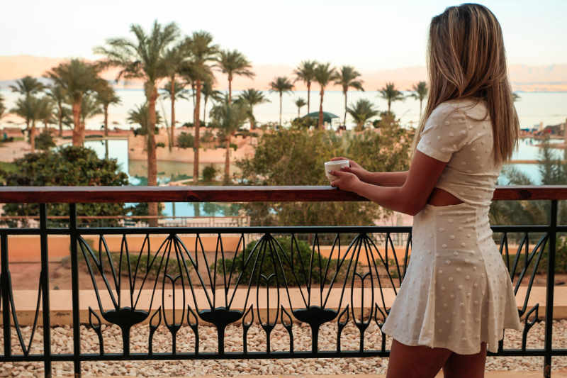 a girl stands in the balcony of mosaique's room and a breakfast with a view to Red Sea