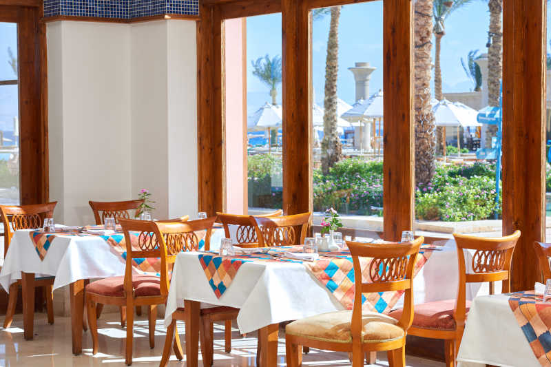 The colorful and wooden decor of the Mediterranean restaurant at Mosaique Beach Resort in Taba Heights